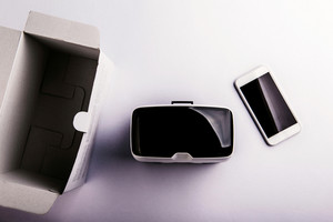 Virtual reality goggles, paper box and smartphone laid on a table. Flat lay. Studio shot on white background.