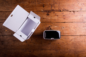 Virtual reality goggles with paper box laid on a table. Flat lay. Studio shot on wooden background.