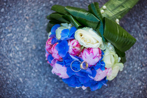 Wedding bouquet and rings laid on the ground