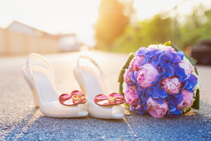 Wedding bouquet and shoes with rings laid on the ground