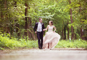 Wedding couple - bride and groom - running down the road