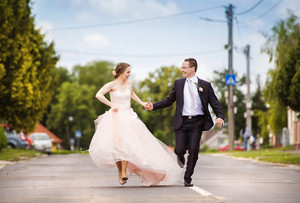 Wedding couple of bride and groom running on the road