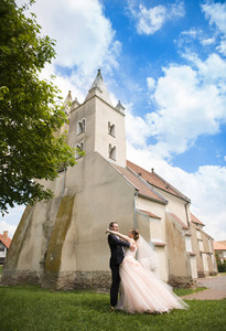 Wedding couple of bride and groom standing by the church.