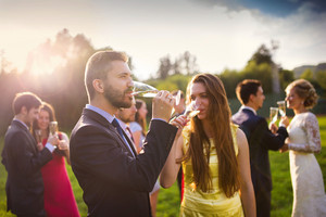 Wedding guests drinking champagne while the newlyweds clinking glasses in the background