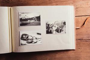 Wedding photos in album. Studio shot on wooden background.