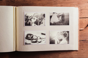 Wedding photos in album. Studio shot on wooden background.