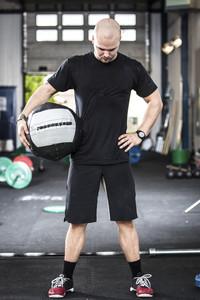 Well trained man with med-ball at the gym