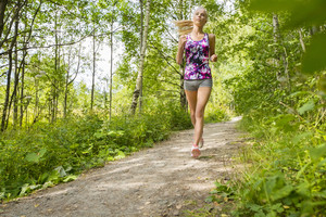 Well trained woman runs alone in the forest