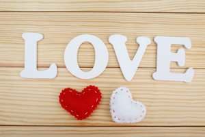 White LOVE text with hearts on wooden background