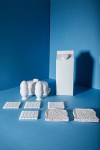 White pack of milk, eggs, butter, cookies and bread slices standing in the corner over blue background