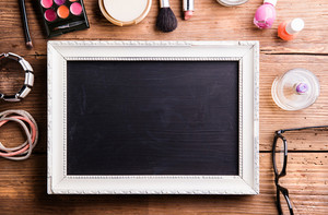 White picture frame with black board in it and various make up products laid on table. Studio shot on wooden background. Flat lay, copy space.