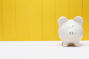 White piggy bank against a yellow wooden wall