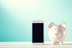 White piggy bank with a smart phone on a blue background