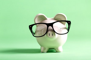 White piggy bank with glasses on a muted green background