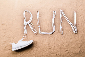 White running shoe and run sign made of shoelaces against sand background, studio shot, flat lay