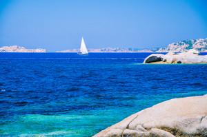 White sailboat, yacht between granite rocks in sea, amazing azure water, Sardinia, Italy