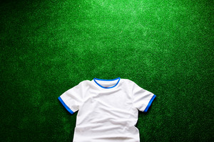 White sports t-shirt against artificial turf, studio shot on green background. Copy space.