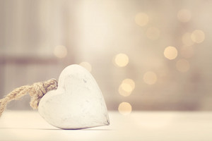 White wooden heart on abstract light background