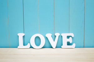 White wooden LOVE text on blue boards background