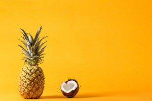 Whole pineapple and fresh coconut on a bright yellow background