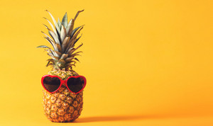 Whole pineapple with sunglasses on a bright yellow background