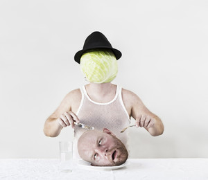 Wierd cabbage man with hat eating a mans head on a plate.