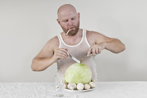 Wierd man eat cabbage and mushrooms while smoking a cigarette.