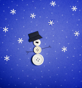 Winter background. Snowman made from buttons and snowflakes on blue background