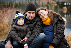 Winter portrait of pregnant mother and father with little boy sitting on pier by the lake