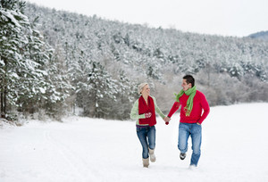 Woman and man are having walk in winter snowy countryside