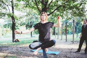 Woman balancing a tightrope or slackline outdoor in a city park in autumn - slacklining, balance, training concept