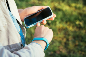 Woman checks data from fitness bracelet on a mobile phone while walking in the park