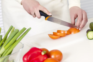 Woman chopping tomatoes in a white kitchen. Prepairing salad with vegetables.