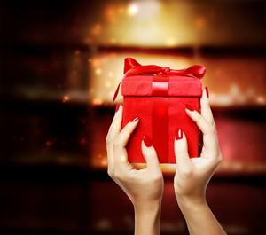 Woman displaying red present box on Christmas