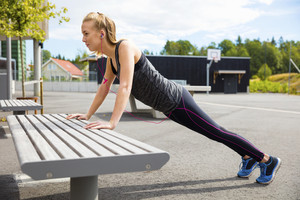 Woman Doing Pushups On Bench In Park