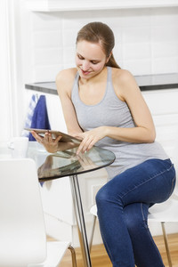 Woman drinking coffee and using tablet in white exclusive kitchen.