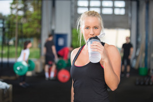 Woman drinking water at fitness gym center
