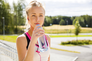 Woman drinks water after running at the countryside