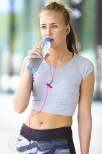 Woman drinks water after workout outdoor in the city
