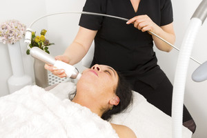 Woman get face treatment at beauty spa