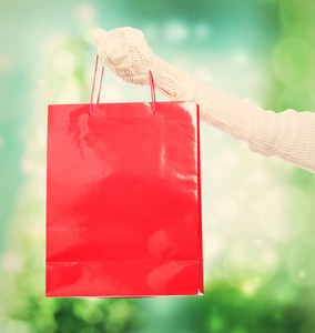 Woman holding a big red shopping bag over green shiny background