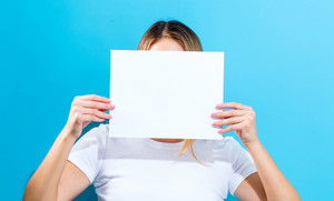 Woman holding a blank sheet of paper in front of her face