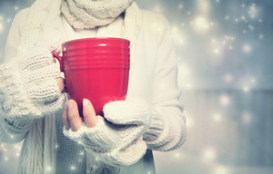 Woman holding a red mug in snowy night