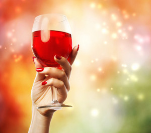 Woman holding a wine glass on abstract light background