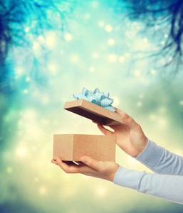 Woman holding and presenting a gift box on teal winter background