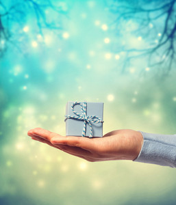 Woman holding and presenting a small blue gift box on teal winter background