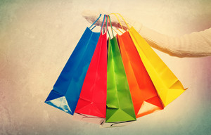 Woman holding colorful shopping bags over vintage style wall background