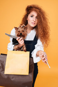 Woman holding cute yorkshire terrier and mobile phone isolated on orange background