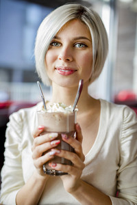 Woman Holding Glass Of Hot Chocolate With Cream In Cafe
