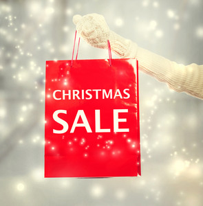 Woman holding red Christmas Sale shopping bag